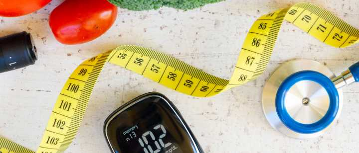 Vegetables with stethoscope, measuring tape and heart rate monitor